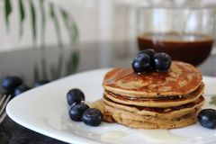 Banana, oat and eggs Pancakes with Blueberries and agave syrup. royalty free stock image