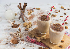 Banana oat smoothie. Peanut and almond butter banana oat smoothie with paper straws on a wooden rustic table stock photo