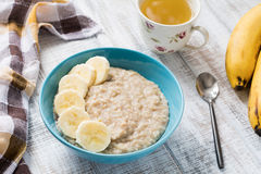 Banana oatmeal porridge and cup of green tea Royalty Free Stock Images