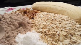 Banana oats and whey protein for cooking. Banana, oats, walnuts, chocolate whey protein and creatine prepared for use used in a recipe Stock Image