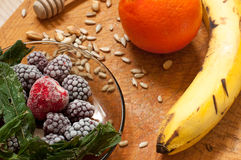 Banana, orange,frozen strawberries blackberries and seeds vivid smoothie ingredients on the background. Banana, orange,frozen strawberries blackberries and seeds royalty free stock photos