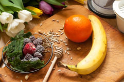 Banana, orange,frozen strawberries blackberries and seeds vivid smoothie ingredients and blender, juicer, tulips on the background. On wooden royalty free stock photos