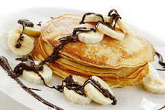 Banana Pancakes. With melted chocolate and powdered sugar.  A delicious indulgent dish Royalty Free Stock Photos