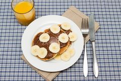 Banana pancakes with chocolate and orange juice Royalty Free Stock Image