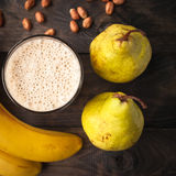 Banana and pear smoothie. Glass of smoothie, some peanuts, fresh bananas and pears on wooden background royalty free stock photos