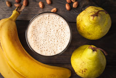 Banana and pear smoothie. Glass of smoothie, some peanuts, fresh bananas and pears on wooden background. Close up royalty free stock image