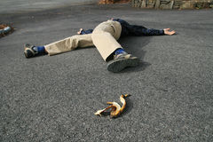 Banana peel accident. A man who had an accident when he slipped on a banana peel lies on the ground Stock Photo