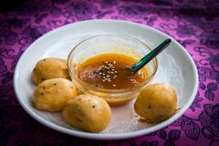 Banana with powder deep fried with syrup sesame sauce in a bowl stock images