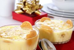Banana Pudding. Old fashioned banana pudding with cookies, banana chunks, and pudding in cut crystal dishes on Christmas decorated table Royalty Free Stock Images