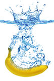 Banana que espirra na água imagem de stock