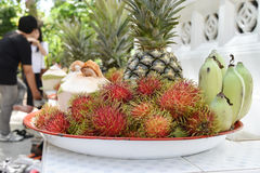 Banana, rambutan, coconut, orange and pineapple in zinc salver Stock Photos