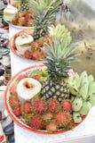 Banana, rambutan, coconut, orange and pineapple in zinc salver Royalty Free Stock Photo
