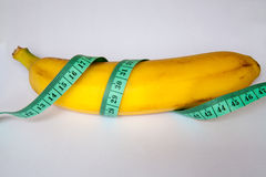 Banana with a ruler Stock Photography