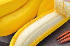 Banana sbucciata su fondo di legno Immagine Stock