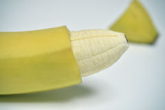 Banana with the skin of its tip removed. Closeup of a banana with the skin of its tip removed depicting a circumcised male member stock image