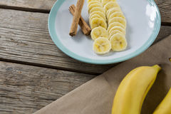Banana and slices of banana with cinnamon stick in plate on wooden table Royalty Free Stock Image