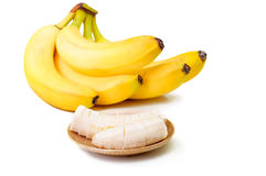Banana slices on a brown plate and bunch of ripe bananas isolate Royalty Free Stock Photography