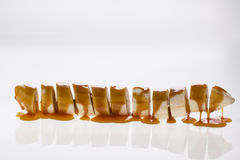 Banana slices with caramel sauce funny. Sliced banana with caramel sauce front of white background Royalty Free Stock Images