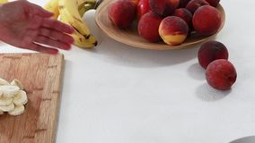 Banana slices on a chopping board close up on white background, woman hands. Fresh fruit platter step by step. Woman is slicing bananas on a wooden cutting board stock footage