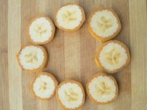 Banana slices circle on wooden background Royalty Free Stock Photos