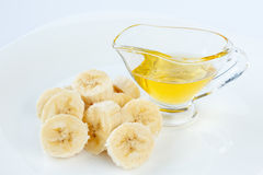 Banana slices and honey in a glass gravy boat Royalty Free Stock Images