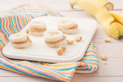 Banana slices with peanut butter on white board Stock Photos