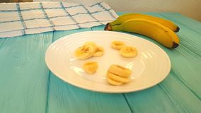 Banana slices on a plate falling slow motion. Dessert stock footage