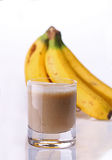 Banana smoothie. In glass with bunch of bananas in the background Royalty Free Stock Images