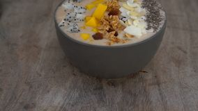 A banana smoothie bowl with dragon fruit, mango, granola, raisin, almond slices, and chia seeds on a wooden background.  stock video footage