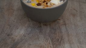 A banana smoothie bowl with dragon fruit, mango, granola, raisin, almond slices, and chia seeds on a wooden background.  stock video