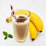Banana smoothie. With chocolate on a old white wooden background Royalty Free Stock Photos