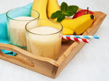 Banana smoothie. And fruits on a wooden background Stock Images