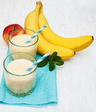 Banana smoothie. And fruits on a wooden background Stock Photo