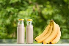 Banana smoothie in glass bottle on green background. Stock Photo
