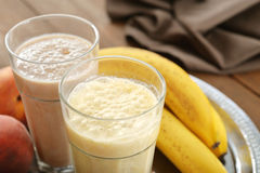 Banana smoothie. In glass with fresh fruits and chocolate on wooden background Stock Photography