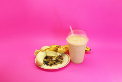 Banana smoothie and granola. Liquefied banana and granola , served in plastic cup and straw Stock Images