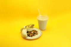 Banana smoothie and granola. Liquefied banana and granola , served in plastic cup and straw Royalty Free Stock Photos