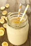 Banana smoothie in jar on wood Stock Photos