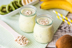 Banana smoothie with kiwi and oats on a light wooden table. Royalty Free Stock Images
