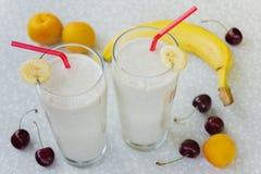 Banana smoothie with milk, cherry, peaches and banana on a white table Stock Photos