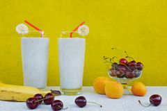 Banana smoothie with milk, cherry, peaches and banana on a yellow background Royalty Free Stock Photos