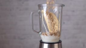 Banana smoothie with oatmeal, yogurt, brown sugar and vanilla milk. Pouring oatmeal in blender, slow motion video stock video