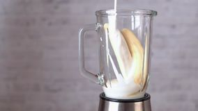 Banana smoothie with oatmeal, yogurt, brown sugar and vanilla milk. Pouring yogurt in blender, slow motion video stock footage