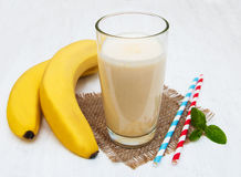 Banana smoothie. On a old white wooden background Stock Photos
