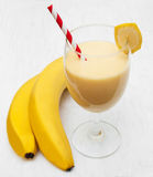 Banana smoothie. On a old white wooden background Royalty Free Stock Photo