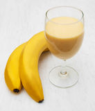Banana smoothie. On a old white wooden background Royalty Free Stock Images