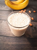 Banana smoothie and peanuts. Smoothie with bananas and some peanuts on wooden background royalty free stock image
