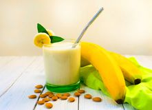 Free Banana Smoothie With Almond Milk. Milk Smoothie With Bananas, And Almond Nuts On A White Wooden Table. Concept Of Vegetarian Prod Royalty Free Stock Image - 156376926