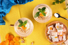 Banana smoothies, Turkish Delight and dried apricots with walnuts on a colored background, top view. Two fruity Royalty Free Stock Image