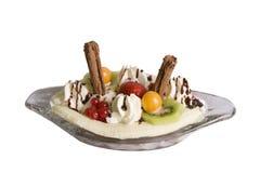 Banana Split Dessert. Banana Split with kiwi fruit, strawberry, redcurrants, physalis, chocolate flakes, cream and chocolate sauce in a glass dish Royalty Free Stock Photos
